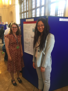 two women, Shelley Staples on left and Wendy Gao on right stand with their research poster at the 2017 Corpus Lingusitics conference.