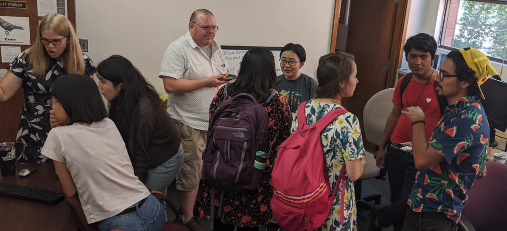 Gathering of people standing in a small office. At left, Shelley Staples demonstrates the Crow interface.